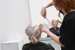 Stylist cuts elderly woman's hairの写真素材 [FYI03637822]