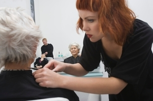 Stylist makes finishing touches to elderly woman's hairの写真素材 [FYI03637839]