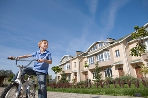 Boy stands with bicycle in new housing developmentの写真素材 [FYI03637859]
