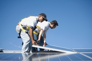 Two men lifting a solar panelの写真素材 [FYI03637911]