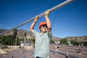 A man lifting a large metal pole on a roof topの写真素材 [FYI03637913]