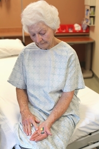 An old lady in a hospital gown  sitting on a bed  lookingの写真素材 [FYI03637927]