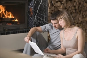 Young couple sit with laptop beside open fireの写真素材 [FYI03637981]
