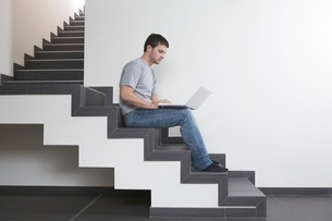 Young man sits on staircase with laptopの写真素材 [FYI03637983]