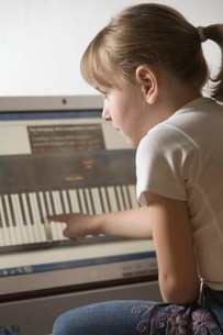 Child leans keywboard on computer with touch screen technoの写真素材 [FYI03637984]