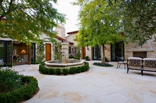 House exterior with a fountain  trees and patio furnitureの写真素材 [FYI03638009]