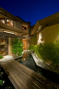 House exterior at night with wooden walkway over waterの写真素材 [FYI03638055]