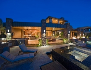 House exterior lit up at night  with patio furnitureの写真素材 [FYI03638056]