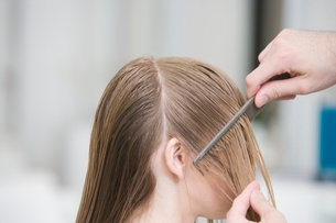 Combing a womans wet hair in the hairdressersの写真素材 [FYI03638081]