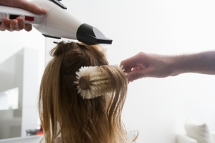 A young woman having her hair dried in the hairdressersの写真素材 [FYI03638091]