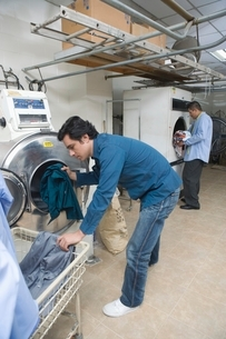 Man loading clothes into the washing machineの写真素材 [FYI03638116]