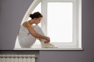 Mid adult woman sits on windowsill with ankles crossedの写真素材 [FYI03638227]