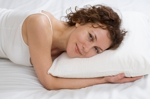 Mid adult woman lies on pillow smiling at cameraの写真素材 [FYI03638237]