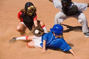 Softball player sliding into home plateの写真素材 [FYI03638258]
