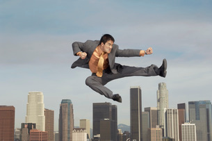 Business man doing martial arts mid-air above cityの写真素材 [FYI03638289]