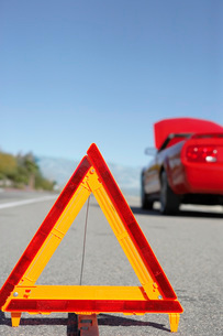 Warning triangle in front of broken down red sports car at sの写真素材 [FYI03638295]