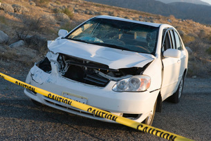 Smashed car cordoned off behind police tapeの写真素材 [FYI03638297]