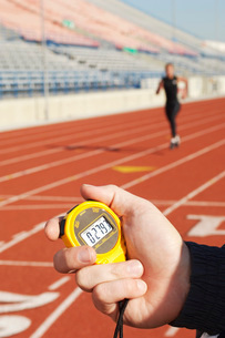 Man holding stopwatch close up of hand timing runner on runnの写真素材 [FYI03638313]