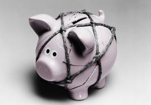 Broken piggy bank reassembled with twineの写真素材 [FYI03638331]