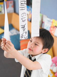 Elementary schoolboy learning to read from hanging paper strの写真素材 [FYI03638350]