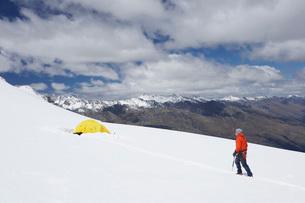 Hiker walking toward tent in snowy mountainsの写真素材 [FYI03638352]
