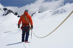 Hiker connected to safety line in snowy mountains back viewの写真素材 [FYI03638354]