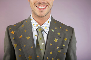 Businessman with gold stars on suit portraitの写真素材 [FYI03638378]