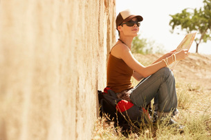 female hiker holding map sitting on ground by rustic houseの写真素材 [FYI03638397]