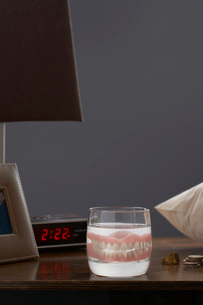 False teeth in glass on bedside cupboardの写真素材 [FYI03638479]