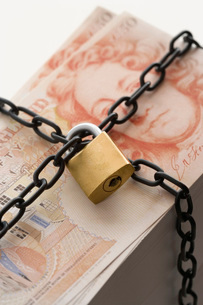Stack of fifty pound notes secured by padlock and chainの写真素材 [FYI03638618]