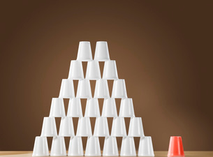 Pyramid of white plastic cups on table next to single red cuの写真素材 [FYI03638631]