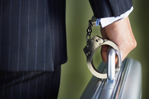 Middle-aged businessman handcuffed to briefcase mid sectionの写真素材 [FYI03638649]