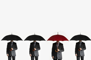 Businessmen holding umbrellas standing side by side one redの写真素材 [FYI03638650]