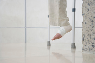 Human foot of person on crutches low sectionの写真素材 [FYI03638666]