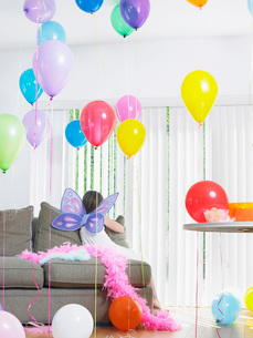 Young girl (7-9) sitting on sofa with balloons wearing fairyの写真素材 [FYI03638706]