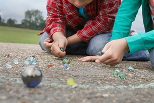 Children (7-9) playing marbles lying in playgroundの写真素材 [FYI03638724]