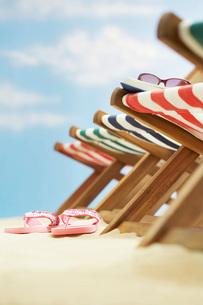 Row of deck chairs on beach focus on flip-flops on groundの写真素材 [FYI03638730]