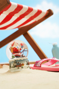 Souvenir santa snow globe under deckchair on beach close upの写真素材 [FYI03638743]