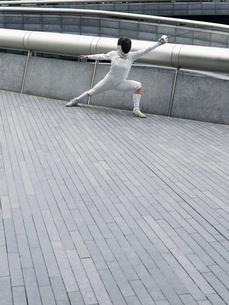 Female fencer lunging outdoorsの写真素材 [FYI03638756]