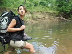 Young woman carrying backpack walking in water looking overの写真素材 [FYI03638767]