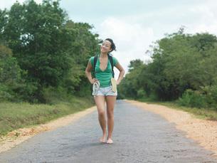 Young woman barefoot walking rural road smilingの写真素材 [FYI03638776]