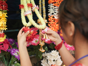 Young woman looking at artificial flowers necklaces back vieの写真素材 [FYI03638784]