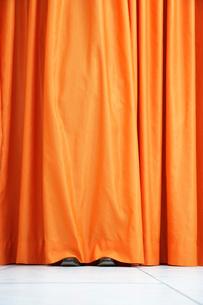Person hiding behind orange curtainの写真素材 [FYI03638809]