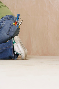 Woman with paintbrush and hand tools in back jeans pocket knの写真素材 [FYI03638822]