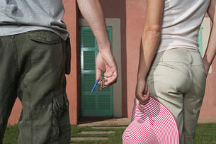 Man and woman in front of house man holding keys woman hatの写真素材 [FYI03638851]