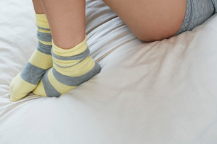 Young woman in underwear on bed low sectionの写真素材 [FYI03638905]