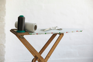Spools of thread and scissors on ironing board indoorsの写真素材 [FYI03638943]