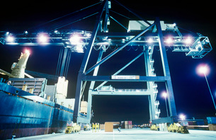 Crane loading container ship at nightの写真素材 [FYI03639016]