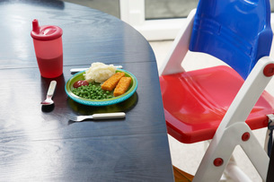 High chair at table with child's dinner close-upの写真素材 [FYI03639069]
