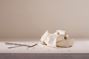 Dish cloth cutlery and crumbs on tableの写真素材 [FYI03639149]